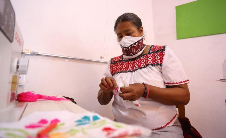 Mujeres otomíes elaboran cubrebocas bordados a mano